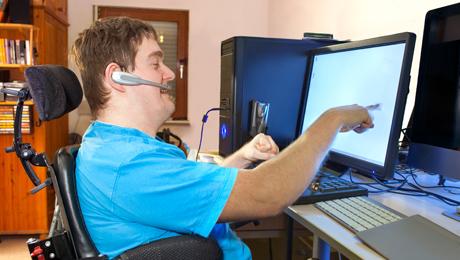 Mies istuu pyörätuolissa tietokoneella ja osoittaa näyttöä.