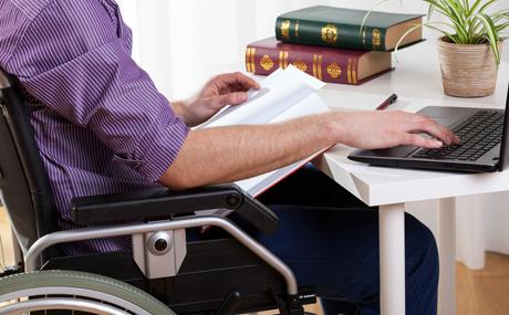 Pyörätuolissa istuva mies istuu tietokoneella ja samalla selaa papereita.