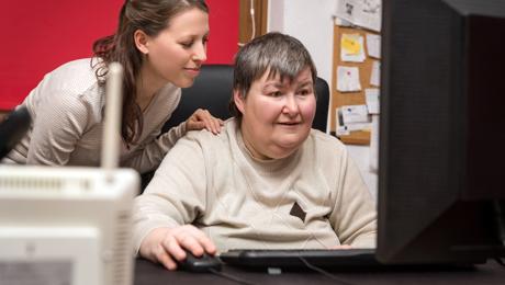 Kaksi ihmistä katsoo tietokoneen näyttöön.