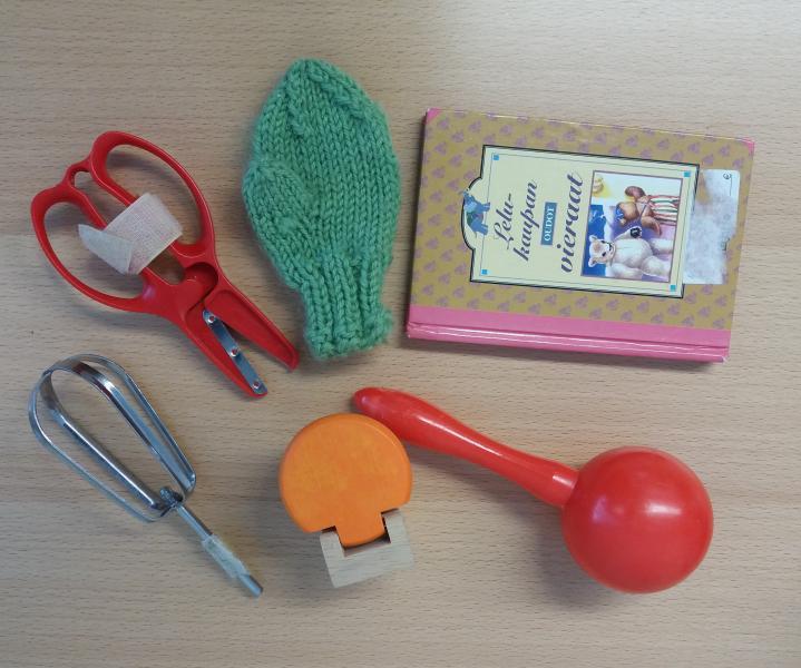 Valokuvassa on kommunikaatiossa käytettäviä esinesymboleja. Ne ovat pienet sakset, lapanen, kirja, keittiövispilä, nukkekodin vessanpönttö sekä marakassisoitin.