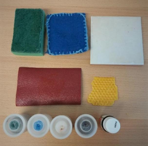 Valokuvassa on kommunikaation tukena käytettäviä erilaisia esineitä. Kuvassa on myös tuoksupurkkeja.