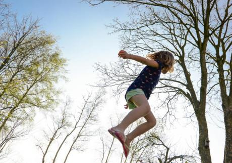 Valokuvassa tyttö hyppii trampoliinilla ulkona.