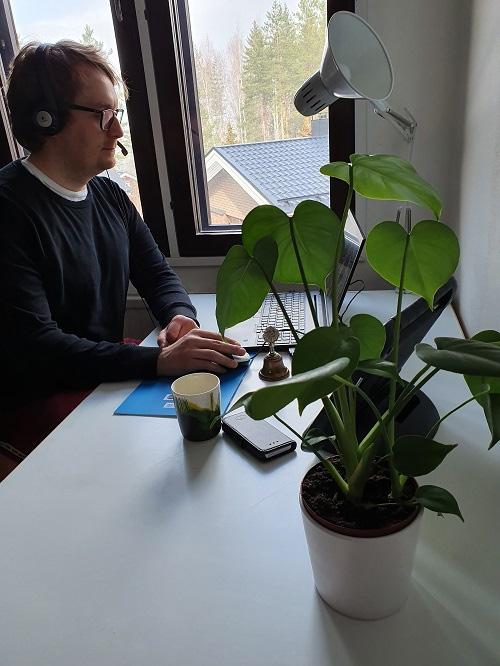 Lauri Räty istuu tietokoneella kuulokkeet päässä ja mikrofoni edessä.