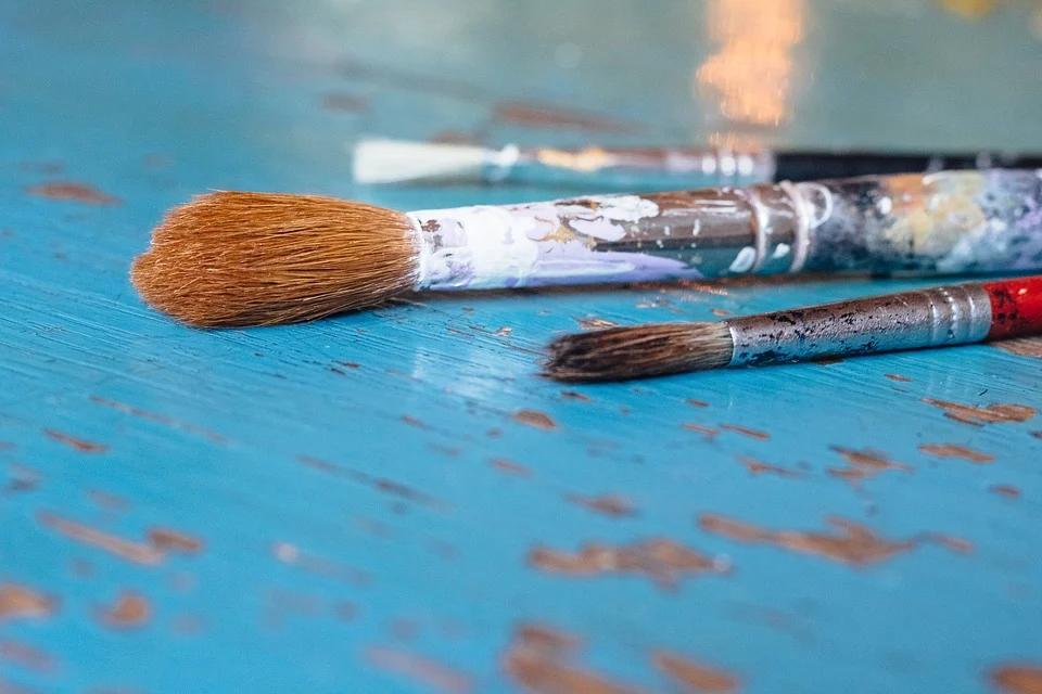 Kuvassa on maalauspensseleitä pöydällä.