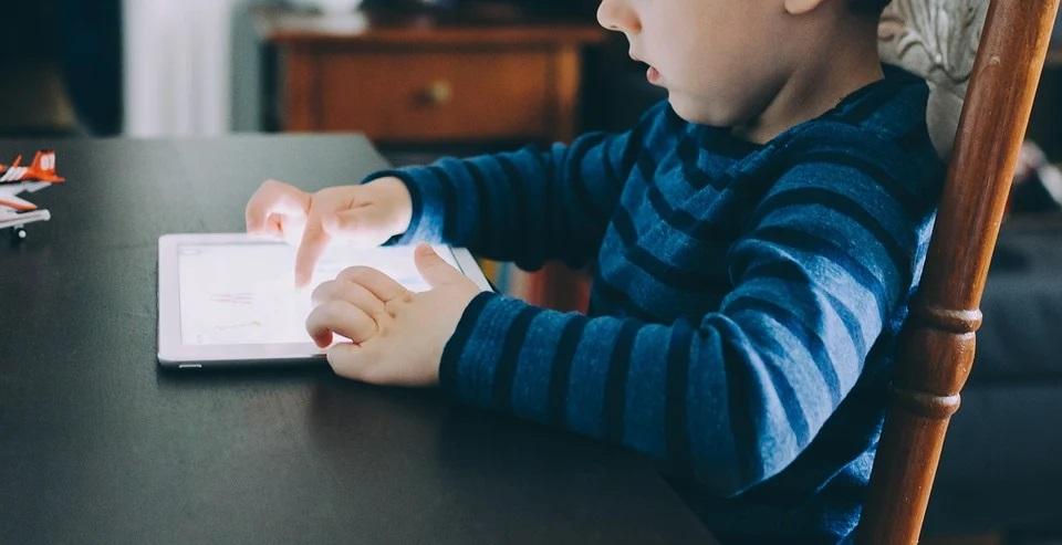 Valokuvassa poika pelaa tabletilla.