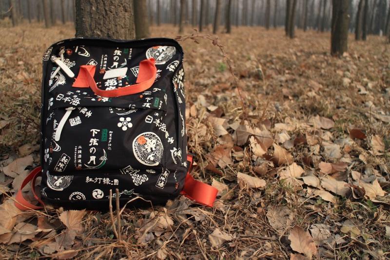 Valokuvassa on koulureppu syksyisessä metsässä.