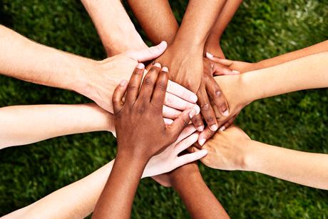 Kuvassa on tumma- ja vaaleaihoisten ihmisten käsiä toistensa päällä.