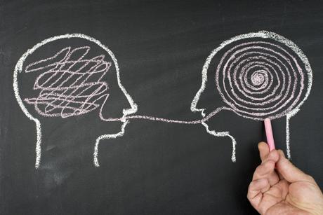 På bilden finns två huvud ritade på en svart tavla och mellan dem löper en tråd.