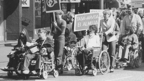 Mustavalkoisessa kuvassa on vammaisia ihmisiä mielenosoituksessa.