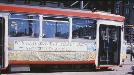 """På bilden finns en spårvagn med texten: """"pois antiikkisesta yhteiskunnasta - yhteiskunta kaikille"""" (slopa det antika samhället – samhället tillhör alla)."""