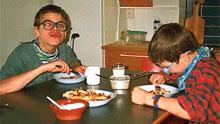 Pojat syömässä lättyjä.