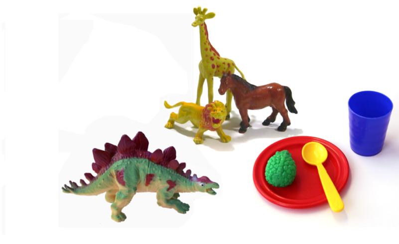 valokuvassa leluesineitä: dinosaurus, kirahvi, leijona, hevonen,  lusikka, lautanen, muki, vihreä esine