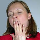 En kvinna gäspar med handen framför munnen och med ögonen fast.
