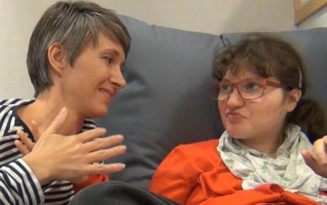 Kaksi aikuista istuvat rinnakkain, kämmenet vastakkain ja katsovat toisiaan.
