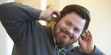 Hymyilevä mies kuuntelee kuulokkeita ja pitää sormilla kiinni kuulokkeista.