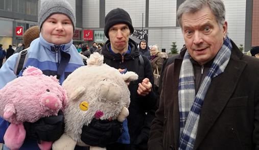 Kuvassa on kaksi henkilöä ja tasavallan presidentti Sauli Niinistö ostoskeskuksen edustalla.