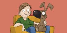 poika ja koira istumassa nojatuolissa.