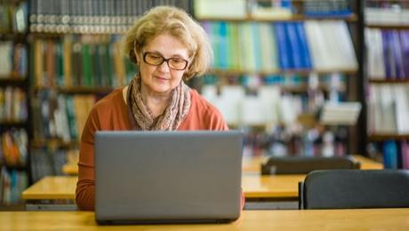 Nainen tietokoneen äärellä kirjastossa.