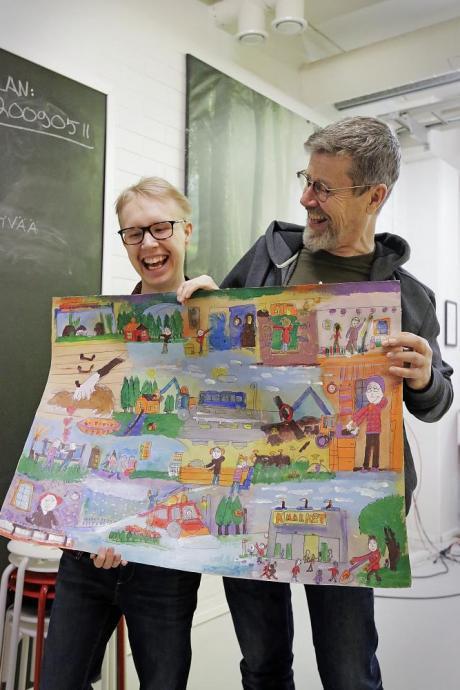 Kaksi hymyilevää miestä pitää käsissään taideteosta.