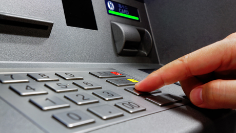 Sormi näppäilee pankkiautomaatin nappuloita.
