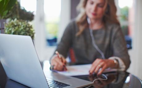 Nainen istuu tietokoneen ääressä ja kirjoittaa muistiinpanoja.