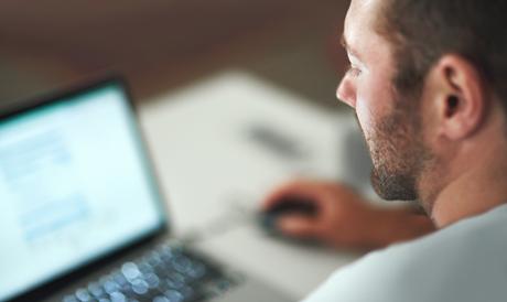 Mies katselee tietokoneen näyttöä.