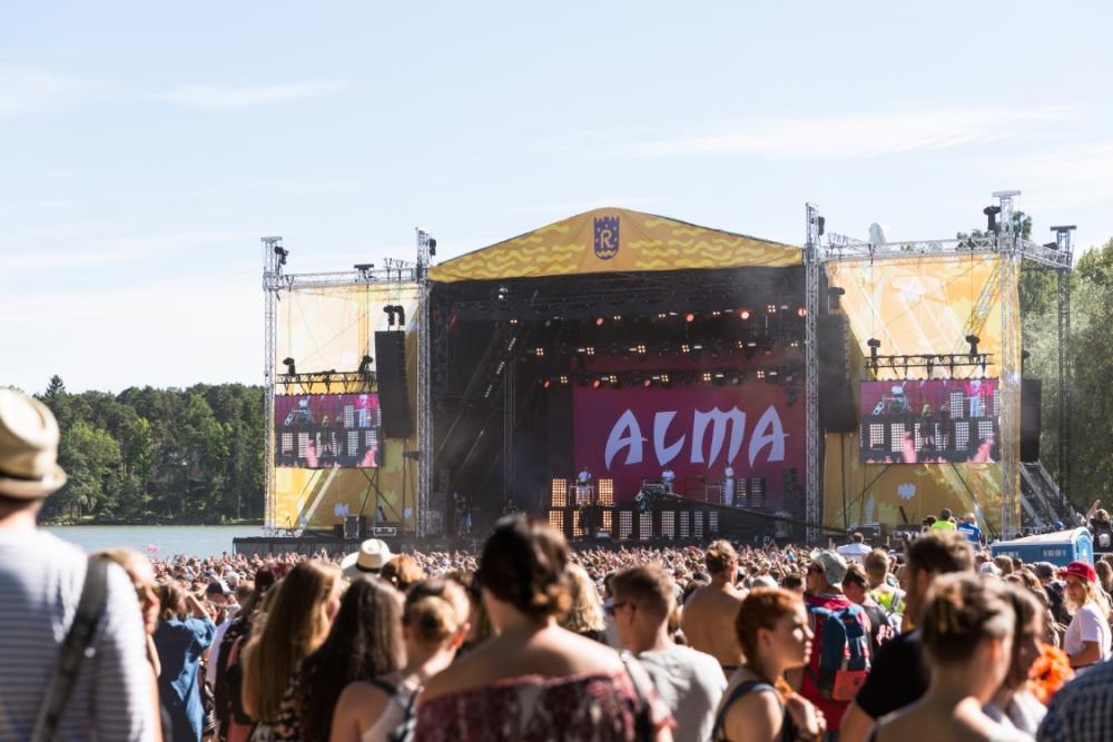 Kuvassa Alma esiintyy Ruisrockissa suurella lavalla, jonka edessä on paljon yleisöä.