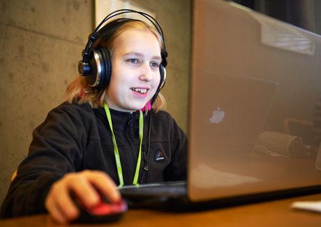 Tyttö istuu tietokoneen ääressä kuulokkeet päässään.