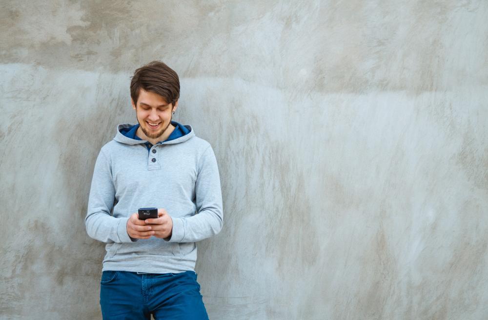 Nuori mies nojaa seinään, käyttää kännykkää ja hymyilee.