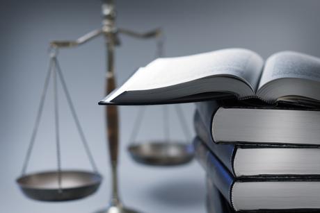 Kuvassa on lakikirja ja taustalla vaaka.