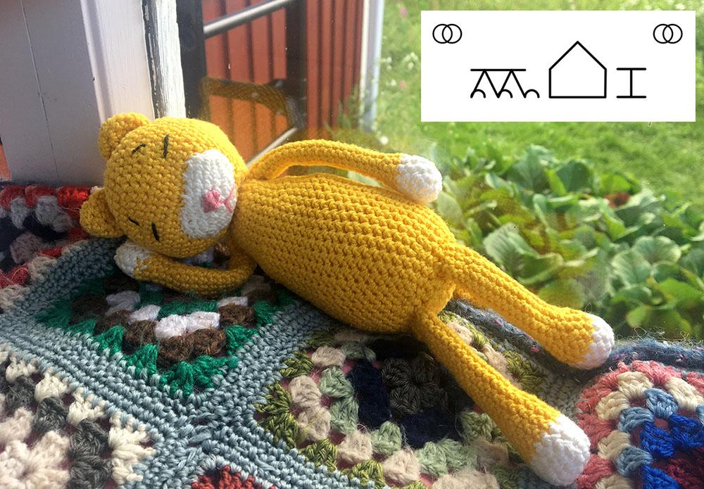 en gul stickad katt vilar i stugan. Det finns också bliss-symboler på bilden.