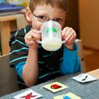 Lapsi juo nokkamukista, pöydällä kuvakortteja