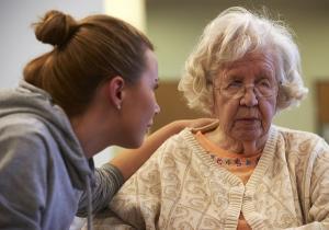 Kvinna böjer sig för att se den äldre och håller armen på hennes axlar.