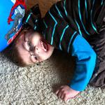 Valokuvassa poika nauraa lattialla