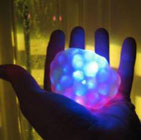 Valokuvassa käden päällä värikäs pallo