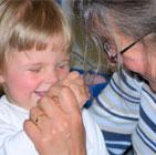 Valokuvassa nainen pitää lasta kädestä