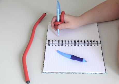 kynä on tuettu käteen muotoiltavan pidikkeen avulla.
