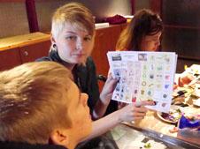 Assistenten visar en symbol från bildtavlan för pojken.