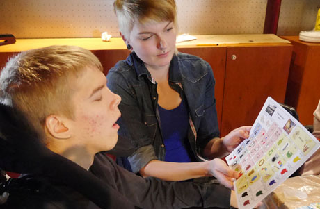 nuori ja avustaja kommunikoivat kuvallisen kommunikointitaulun avulla