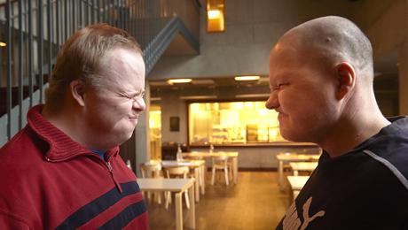 Två män grimaserar åt varandra.