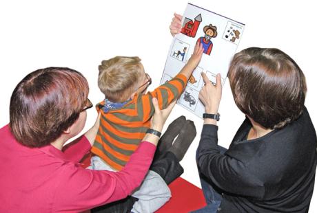 Två vuxna och ett barn som pekar på en tecknad bild från en sångtavla.