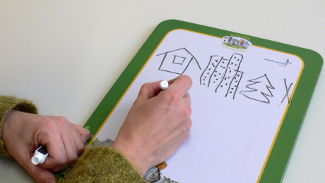 pyyhittävä kirjoitusalusta, johon piirretty kuvat mökki, kerrostalo, kuusipuu ja rasti