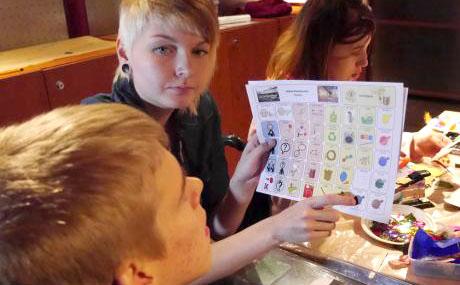 Assistenten pekar på en bild på kommunikationstavlan och ser på den unga som hon visar bilden för.