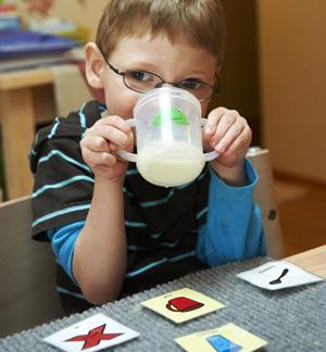 Pojken dricker från muggen, på bordet finns kommunikationsbilder.