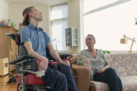 Pyörätuolissa istuva poika ja äiti.