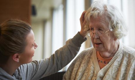 Työntekijä kumartuneena ikäihmistä kohti ja koskettaa hänen hiuksiaan