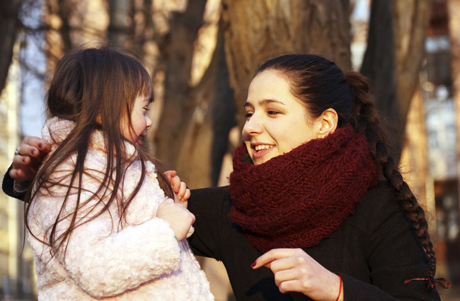 Äiti on kyykistynyt lapsen eteen, molemmat hymyilevät ja katsovat toisiaan.
