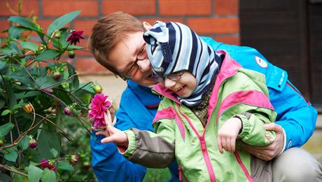 Pojken och mamman ser och doftar på blomman på gården.