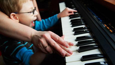 Pojken spelar piano med en vuxen, bådas händer är på tangenterna.