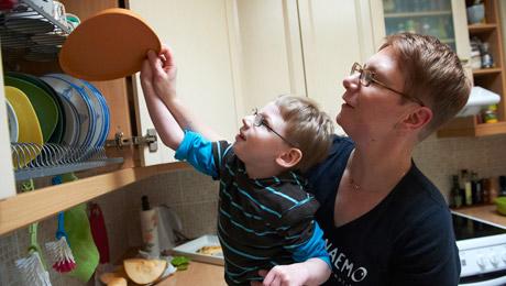 Pojken och mamman sträcker sig efter och tar ut en tallrik ur torkskåpet.